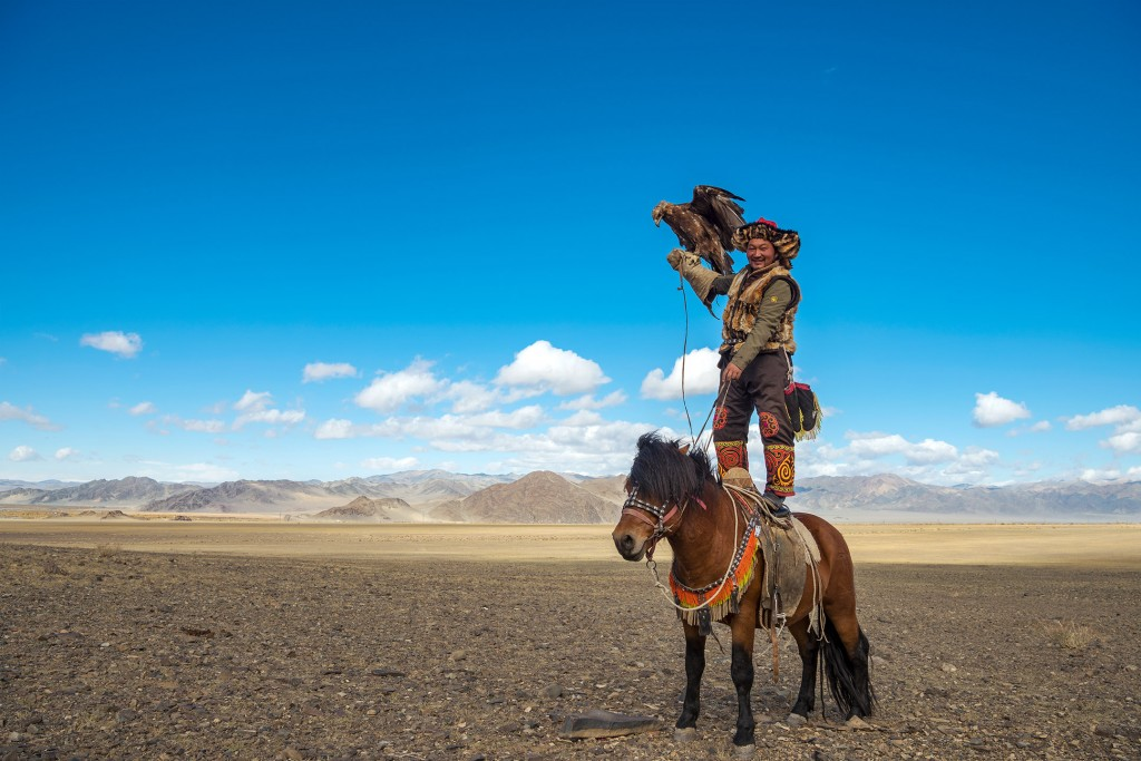 Alpamys Dalaikhan, a burkitshi (eagle hunter) demonstrates his dexterity, deftly standing atop his horse while his golden eagle balances on his arm in Bayan-Ölgii Province in western Mongolia on September 29, 2017.  Alpamys was in Bayan-Ölgii for the Golden Eagle Festival, an annual gathering and celebration of the burkitshi.  Alpamys posed for this portrait at the request of the photographer.
